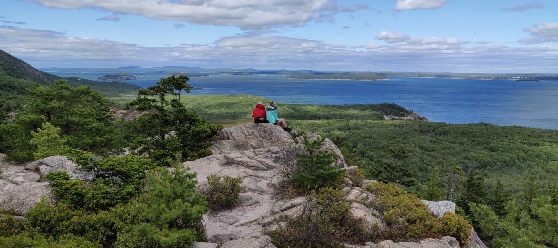 Panoramic view from rocky mountaintop, with water and distant islands, and a couple resting on a rock in distance taking in the view