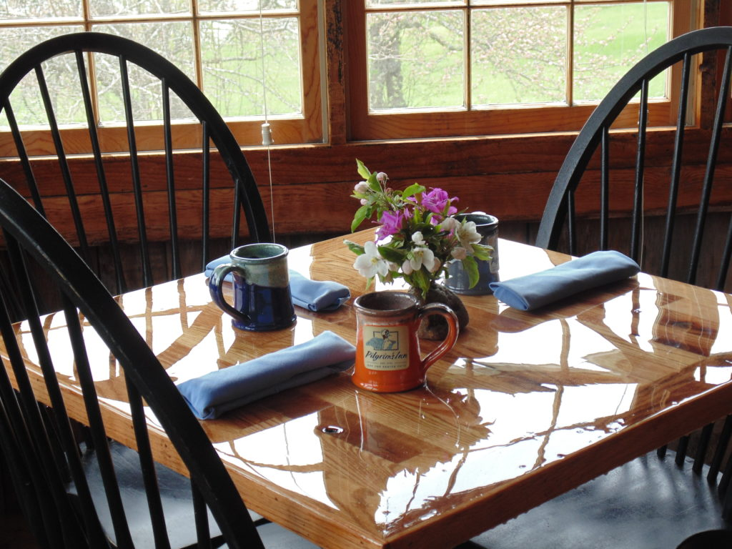 A wood dining table set with blue napkins, flowers, and colorful Pilgrim's Inn mugs, with black chairs and sunlight coming through windows.