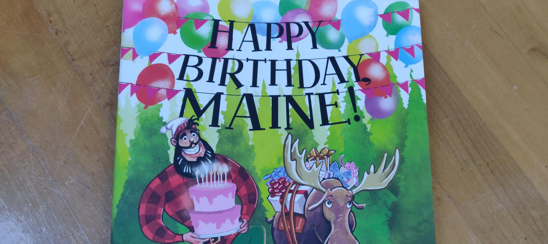 Book cover with title HappyBirthday, Maine! with sketch of Paul Bunyan and Moose
