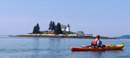 A water view with a man in an orange kayak, and an island beyond that has trees, a house, and a lighthouse