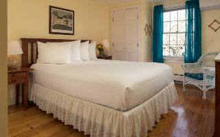 a crisp bed made with white linens in a room with cream walls, a window with teal curtains and a closet