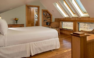 A guest room with wood floor, sloped ceiling with skylights, a door to the bathroom, pale green walls and crisp white bed linens