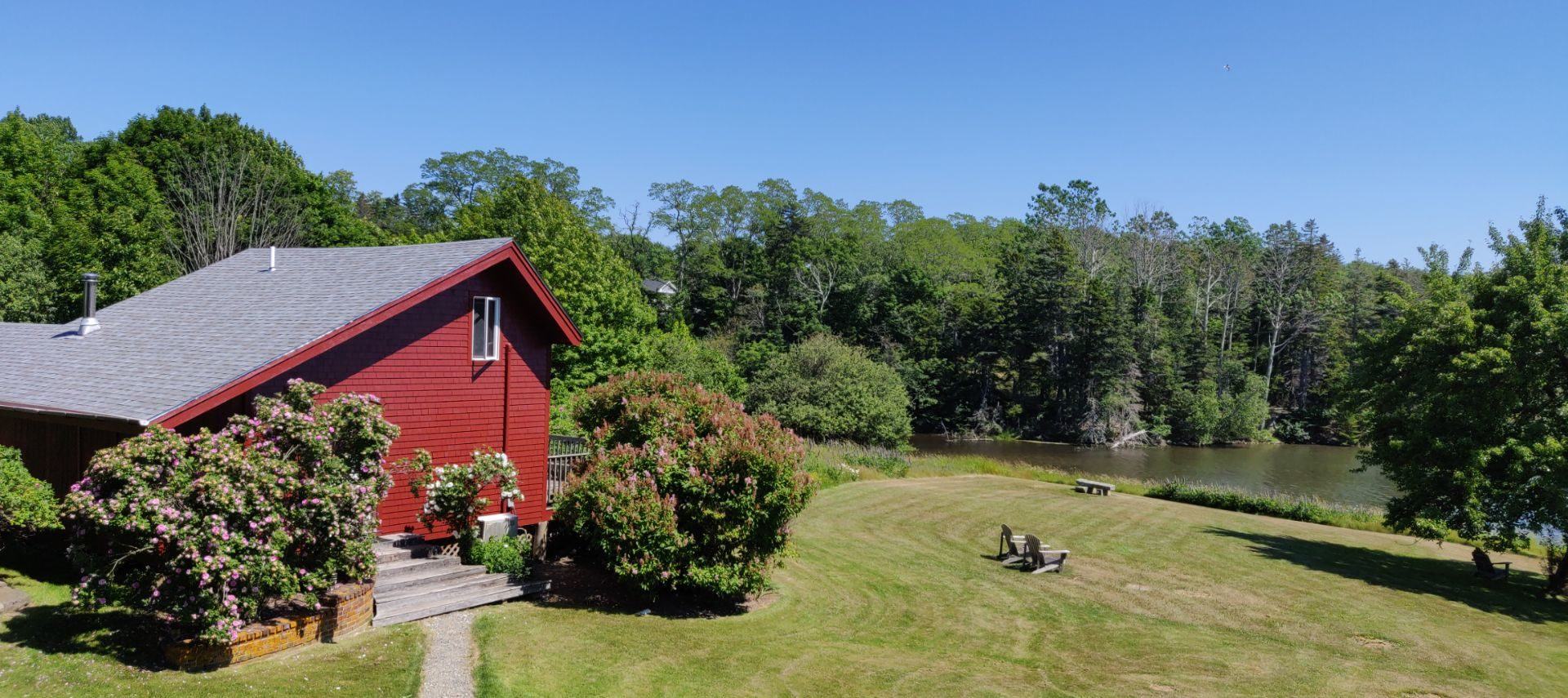 landscape view of red Rugosa Rose Cottage with lawn, lawn furniture, a stone bench, trees and pond