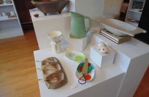 Artisan pieces made out of wood and clay set out for purchase on top of large white display boxes