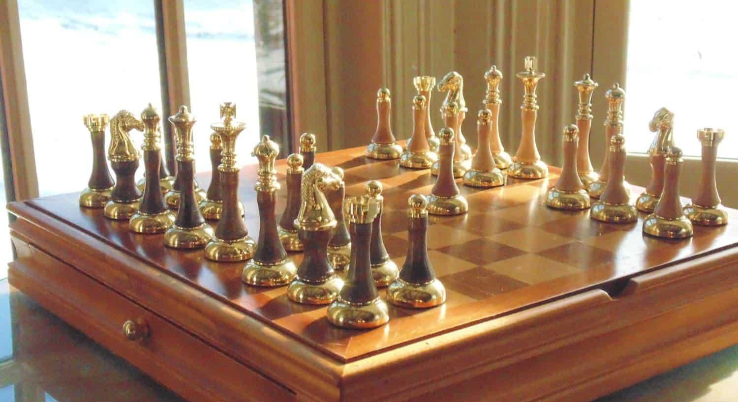 Wooden chess board on top of wooden box with bronze and wood chess pieces