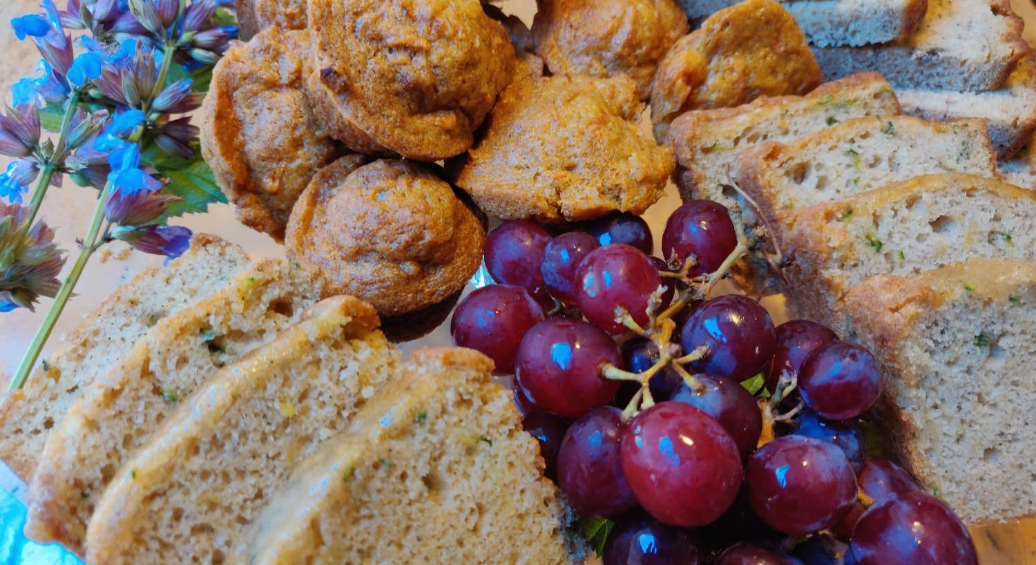 Close up view of breads and muffins and purple grapes