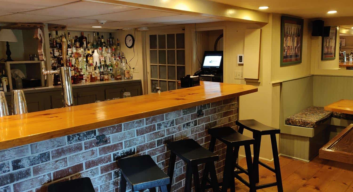 Wooden bar with brick underneath, black bar stools, multiple bottles of liquor behind the bar, and other seating
