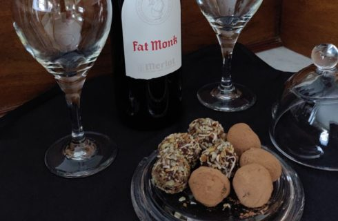 Close up view of wine glasses, glass dish with chocolate truffles, and bottle of Merlot