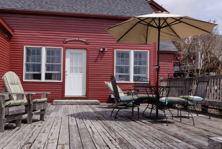 Large wooden deck with adirondack chairs, patio table, patio chairs, and patio umbrella