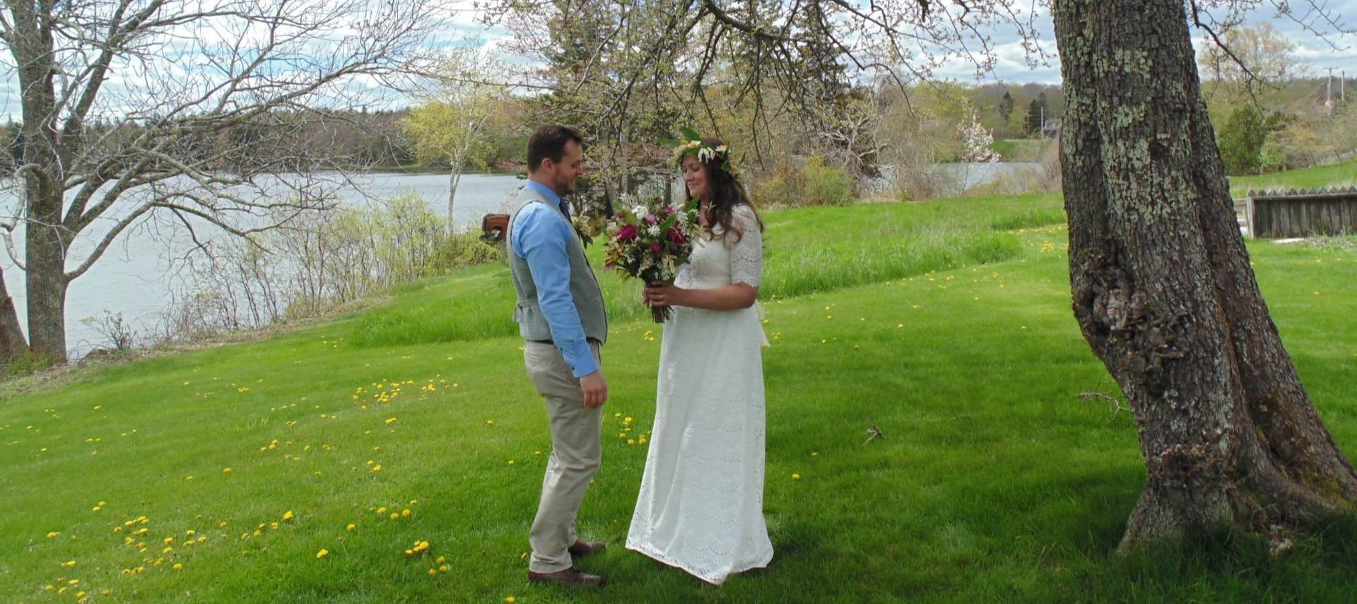 Bride in white dress and groom in blue shirt, gray vest, and khakis standing on green grass surrounded by trees with a body of water in the background