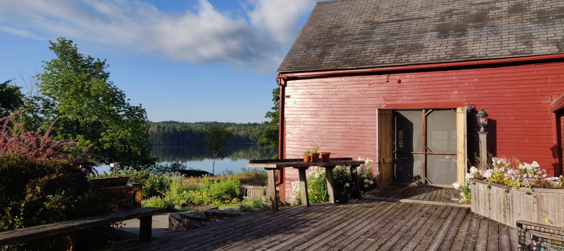 Exterior view of property painted dark red with a wooden deck surrounded by flowers, plants, and trees with a body of water and trees in the background