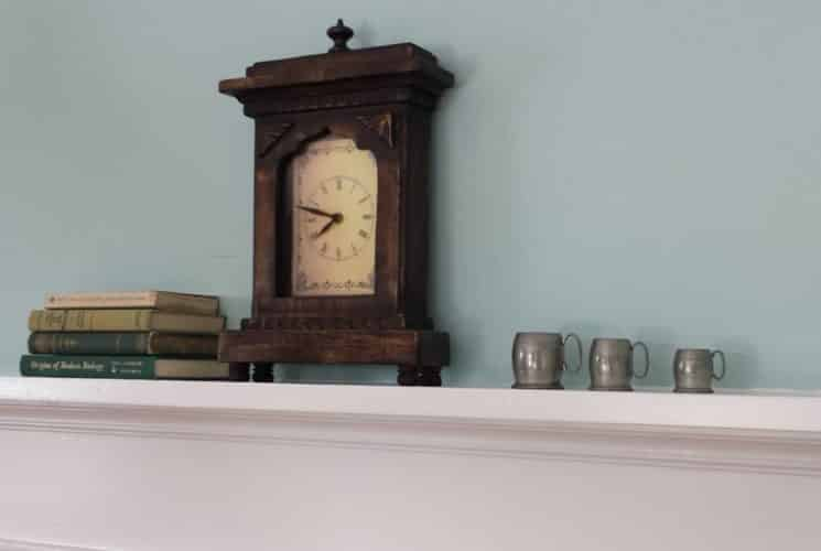Close up view of old wooden mantel clock, books, and sliver cups on a white mantel with blue wall in the background