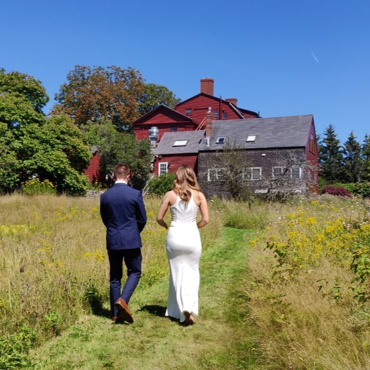 Groom in navy suit and bride in white dress walking through a grassy field toward the property painted dark red