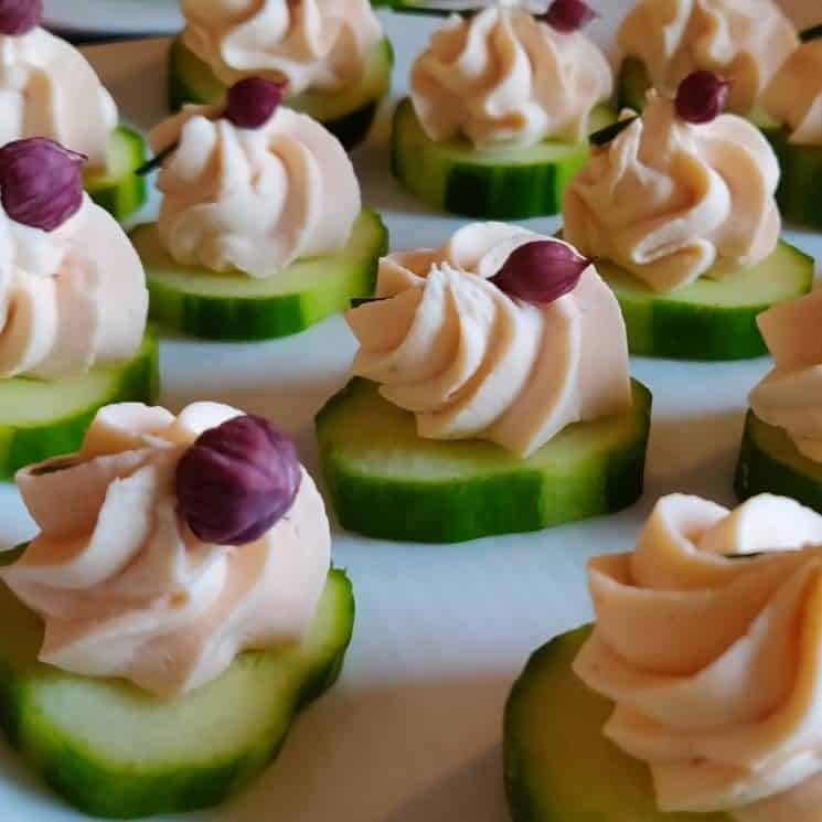 Green cucumber slices with decorative pink cream cheese spread on top