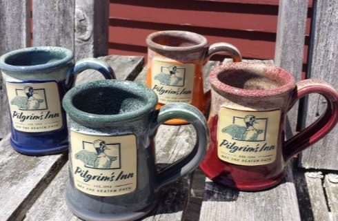 Blue, gray, orange, and red stoneware coffee cups with Pilgrim's Inn logo on them